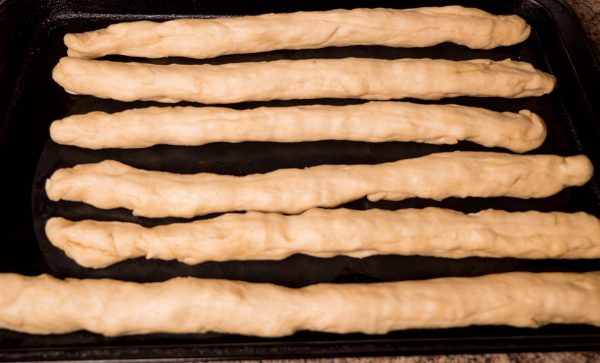 pieces of challah dough cut into strips ready to be braided