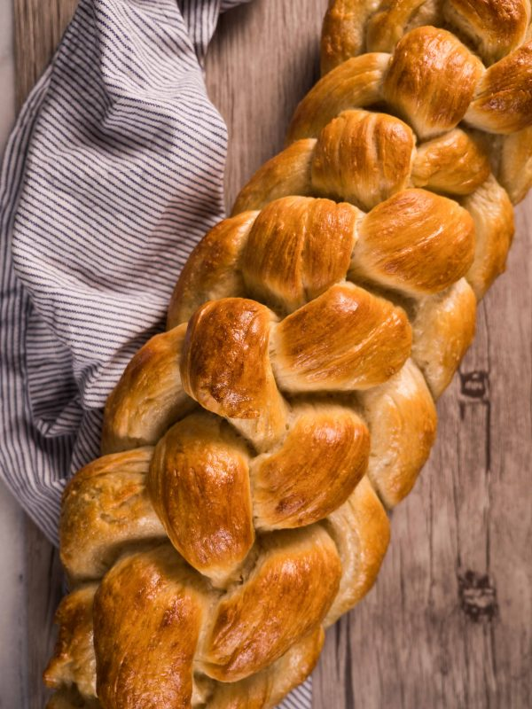 Golden brown baked challah bread next to a blue towel